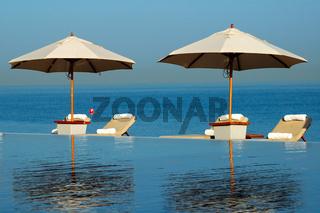 Liegestühle zwischen Swimmingpool und Meer