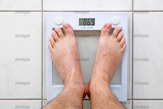 Men's feet on a bathroom scale