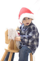 Christkind, Junge mit Schaukelpferd zu Weihnachten