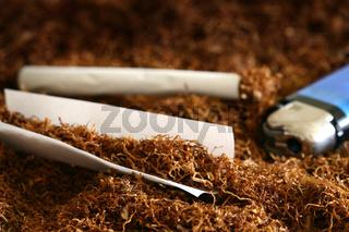 Blättchen gefüllt mit Tabak und Feuerzeug liegt auf Tabakhaufen, leave full of tabacco and lighter lie on tabaccopile