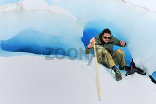 Touristin klettert aus einer Eishoehle heraus