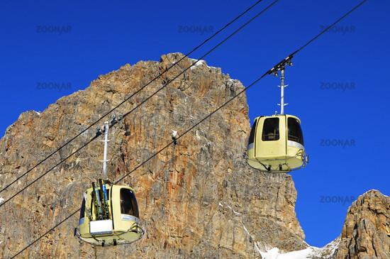 Kabinen einer Seilbahn mit Skis vor einer Felswand