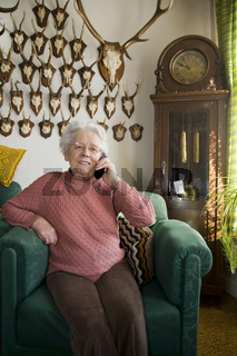 Seniorin telefoniert im Wohnzimmer