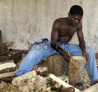 Holzschnitzer zeichnet Skizze auf einem Holzblock