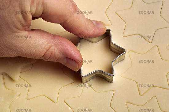 cookie dough is cut out by hand