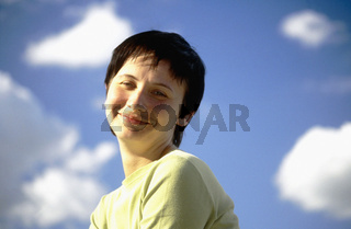 A girl against blue sky with clouds, smiling