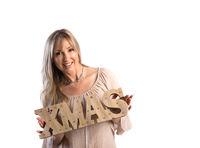 Festive smiling woman holding Xmas word on white background  Christmas Seasonal