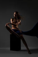 Slim brunette with blue cloth nude on a cube