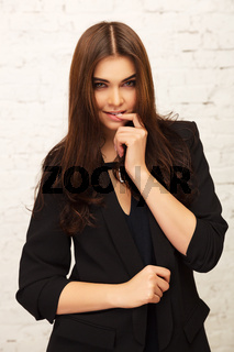 Young fashion woman in black jacket next to brick wall