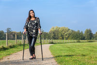 Disabled woman walks on crutches in nature