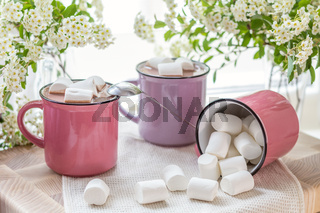 Marshmallows on top of hot cocoa in pink cups
