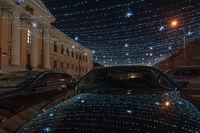 Part of a winter street lit by garlands