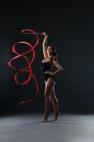 Gymnast posing at camera while dancing with ribbon