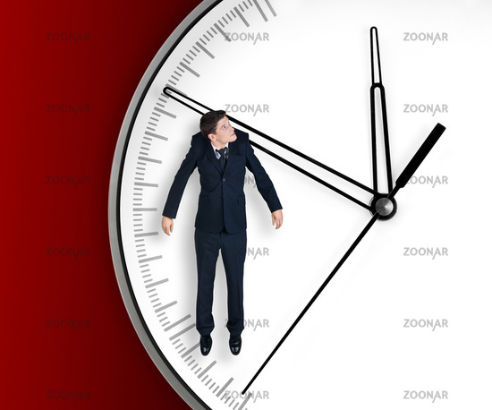 Businessman hangs on an arrow of clock.