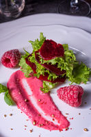 Carpaccio of baked red pray with green salad and raspberry