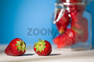 Close up of two strawberries on a table with blue background