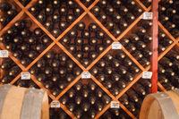 Several Varietal Wine Bottles and Barrels Age Inside Cellar