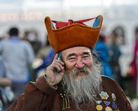 Elderly man with beard, head-dress and medals is talking on a mobile phone, Ulaanbaatar, Mongolia