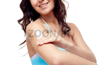 happy young woman in swimsuit applying sunscreen
