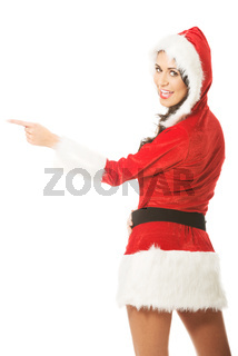 Back view of santa woman pointing to the left, looking on a camera