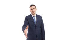 Banker broker or business man making handshake gesture as deal partnership concept
