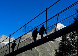 Wanderer im Gegenlicht auf der Charles Kuonen Hängebrücke, Randa, Wallis, Schweiz