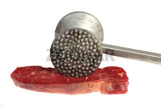 rohes Steak und Fleischklopfer isoliert auf Weiß