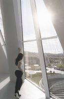 Woman looking outside on big windows