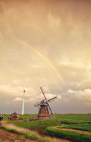 rainbow over Dutch windmill at sunset