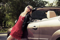 Happy young blond woman at the car