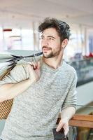 Junger Mann mit Einkaufstüten beim Shopping