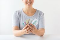 happy woman holding packs of pills
