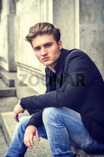 Attractive blue eyed, blond young man sitting on stair steps