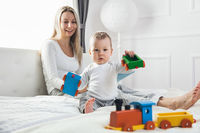 Happy mother with her cute little child on the bed having a good time