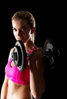 Young sweat woman woman lifting dumbbells