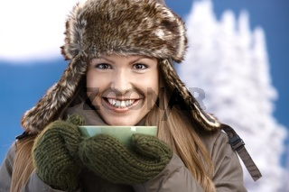 Pretty girl dressed up warm drinking tea smiling