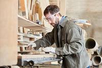 Schreiner schleift Holz am Bandschleifer