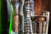 Composition with glass and bottles of mineral water.