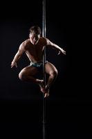 Young fair athletic man exercising on pylon