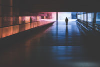 silhouette of a person walking in a dark tunnel