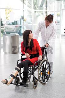 Frau mit Gipsbein, Rollstuhl und Pflegerin