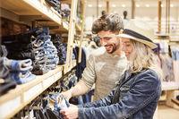 Junges Paar beim Shopping vor der Jeans Auswahl