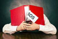 Employee with SOS flag hiding face behind file folder