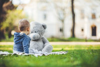 Best of friends. Sweet little toddler playing outdoors with his teddy bear