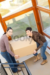 Women carrying cardboard box
