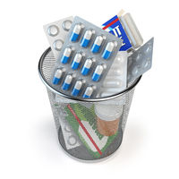 Pills, capsules and medicines thrown in the dustbin isolated on white. End of treatment or healthy lifestyle concept.