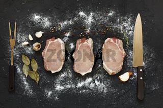 Three slices of raw meat, Raw, T-bone Steak, fresh herbs, SALT, garlic, onion, pepper on a dark stone background, top view, space for text, closeup