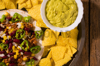Mexican tortillas with meat, red beans, Jalapeno pepper, nachos chips and salsa guacamole