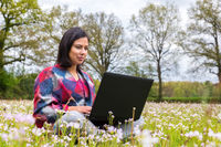 Woman sits with laptop in blooming meadow