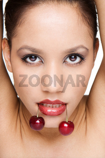 portrait of woman on white holding red cherries on her lips